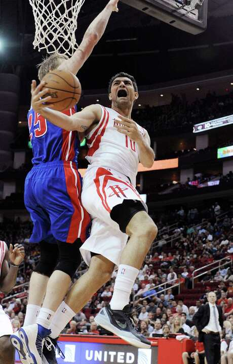 The Rockets' Carlos Delfino, right, is forced into an awkward shot attempt by the Pistons' Kyle Singler. Photo: Pat Sullivan, STF / AP