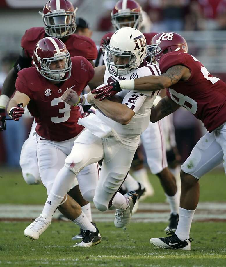 Texas A&M quarterback Johnny Manziel (2) is stopped after a first down run by Alabama defensive back Dee Milliner (28) and  defensive back Vinnie Sunseri (3)during the first half of an NCAA college football game at Bryant-Denny Stadium in Tuscaloosa, Ala., Saturday, Nov. 10, 2012. (AP Photo/Dave Martin) Photo: Dave Martin, Associated Press
