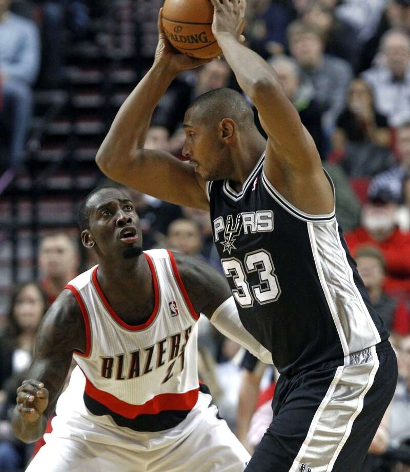 Portland Trail Blazers center J.J. Hickson, left, defends San Antonio Spurs center Boris Diaw, from France, during the first half of their NBA basketball game in Portland, Ore., Saturday, Nov. 10, 2012. (AP Photo/Don Ryan) (Associated Press)