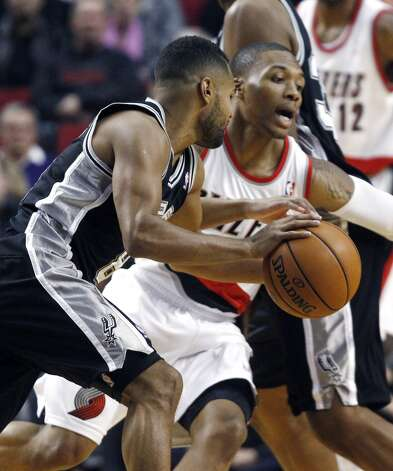 San Antonio Spurs guard Patty Mills, left, drives on Portland Trail Blazers guard Damian Lillard during the first half of their NBA basketball game in Portland, Ore., Saturday, Nov. 10, 2012. (AP Photo/Don Ryan) (Associated Press)