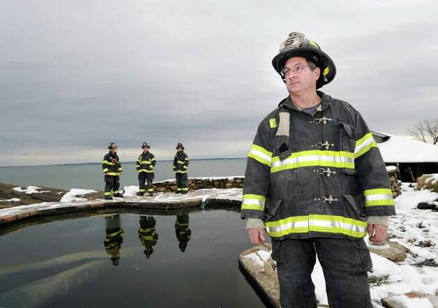 At right, Lt. John Chimblo of the Greenwich Fire Department stands by the pool of the incinerated Long Island Sound watefront mansion at 45 Binney Lane in Old Greenwich, Thursday afternoon, November 8, 2012. Chimblo and and fellow firefighters Adam Jakubowski, Shawn Murphy and Steve Lanzarone, background, left to right, were the first to arrive on the scene of the fire during the height of Hurricane Sandy. Two other homes on the surrounding property caught fire from the hurricane winds and burned to the ground. Photo: Bob Luckey / Greenwich Time