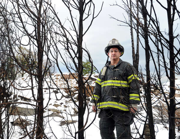Lt. John Chimblo of the Greenwich Fire Department stands near a burned hedgerow with the rubble of the incinerated watefront mansion at 45 Binney Lane visible in the background in Old Greenwich, Thursday afternoon, November 8, 2012. Chimblo and four other Greenwich firefighters were the first to arrive on the scene of the fire during the height of Hurricane Sandy. Two other homes on the surrounding property caught fire from the hurricane winds and burned to the ground. Photo: Bob Luckey / Greenwich Time
