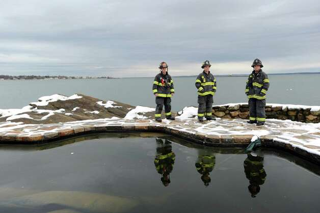 Greenwich Firefighters Adam Jakubowski, Shawn Murphy and Steve Lanzarone, left to right, stand by the pool of the incinerated Long Island Sound watefront mansion at 45 Binney Lane in Old Greenwich, Thursday afternoon, November 8, 2012. These firefighters were among the first to arrive on the scene of the fire during the height of Hurricane Sandy. Two other homes on the surrounding property caught fire from the hurricane winds and burned to the ground. Photo: Bob Luckey / Greenwich Time