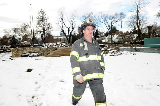 Lt. John Chimblo of the Greenwich Fire Department walks among the ruins of the incinerated watefront mansion at 45 Binney Lane in Old Greenwich, Thursday afternoon, November 8, 2012. Chimblo and four other Greenwich firefighters were the first to arrive on the scene of the fire during the height of Hurricane Sandy. Two other homes on the surrounding property caught fire from the hurricane winds and burned to the ground. Photo: Bob Luckey / Greenwich Time