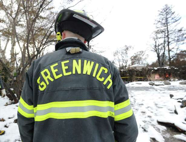 Greenwich Firefighter Adam Jakubowski stands among the ruins of the incinerated watefront mansion at 45 Binney Lane in Old Greenwich, Thursday afternoon, November 8, 2012. Jakubowski and four other Greenwich firefighters were the first to arrive on the scene of the fire during the height of Hurricane Sandy. Two other homes on the surrounding property caught fire from the hurricane winds and burned to the ground. Photo: Bob Luckey / Greenwich Time