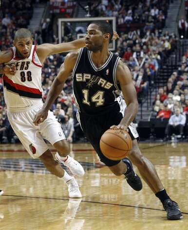 San Antonio Spurs guard Gary Neal, right, drives to the basket past Portland Trail Blazers forward Nicolas Batum, from France, during the second half of their NBA basketball game in Portland, Ore., Saturday, Nov. 10, 2012.  Neal came off the bench to lead the Spurs with 27 points and beat the Trail Blazers 112-109.(AP Photo/Don Ryan) (Associated Press)