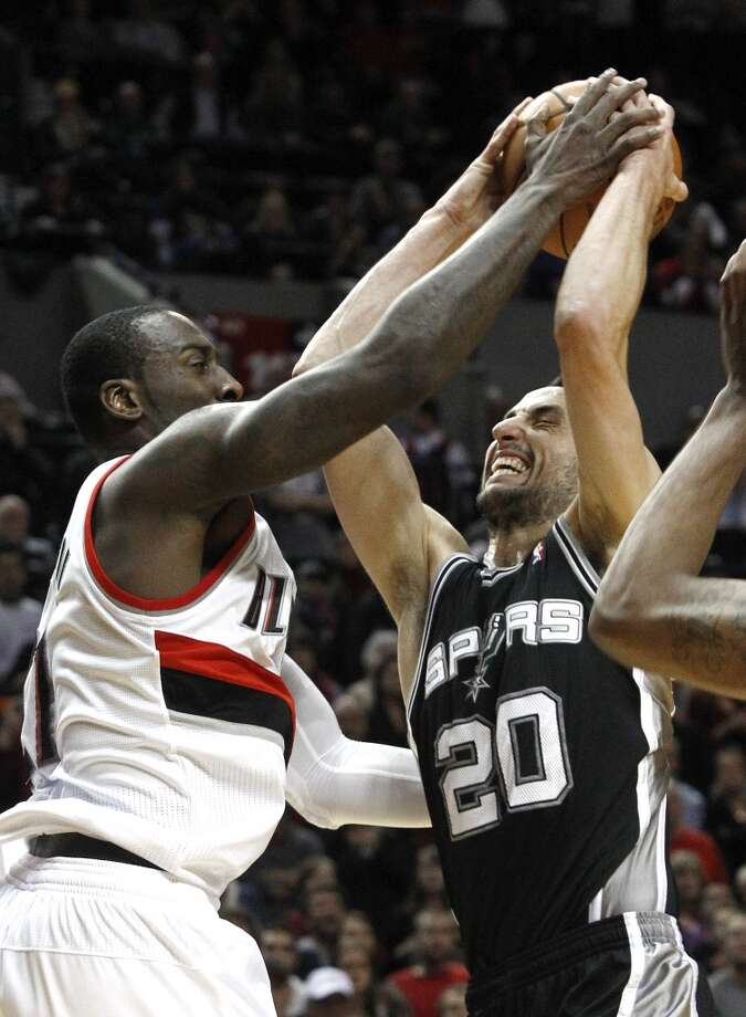 San Antonio Spurs forward Manu Ginobli, right, from Argentina, is fouled going to the basket by Portland Trail Blazers center J.J. Hickson during the second half of their NBA basketball game in Portland, Ore., Saturday, Nov. 10, 2012.  Ginobli scored 17 points coming off the bench as the Spurs won 112-109.(AP Photo/Don Ryan) (Associated Press)