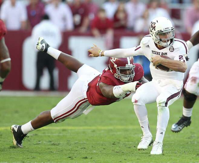 Texas A&M quarterback Johnny Manziel (2) evades the tackle of Alabama defensive lineman Ed Stinson (