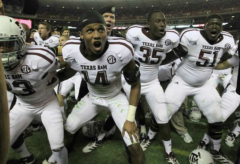 Texas A&M players sing the Aggie War Hymm as they celebrate after beating Alabama during a college f