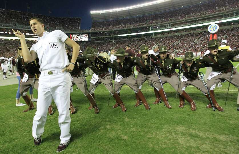 A Texas A&M yell leader and cadets during a cheer in the second half of a college football game at B