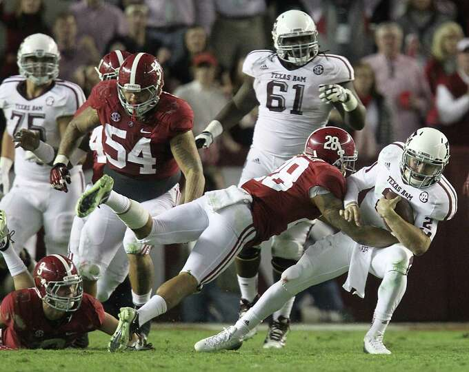 Texas A&M quarterback Johnny Manziel (2) gets tackled by Alabama defensive back Dee Milliner (28) du