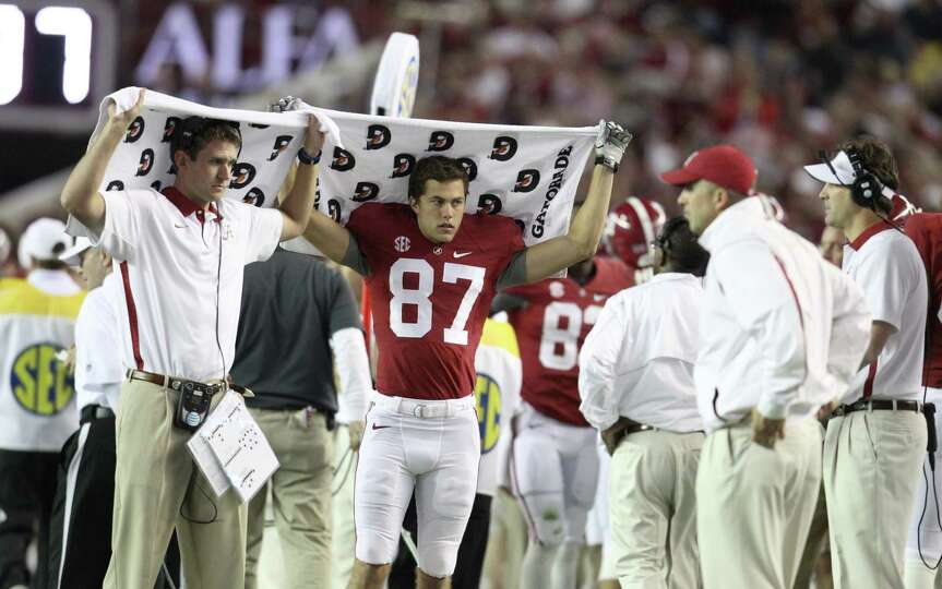 Alabama wide receiver Parker Barrineau (87) and a coach try to shield as a play is called from the s