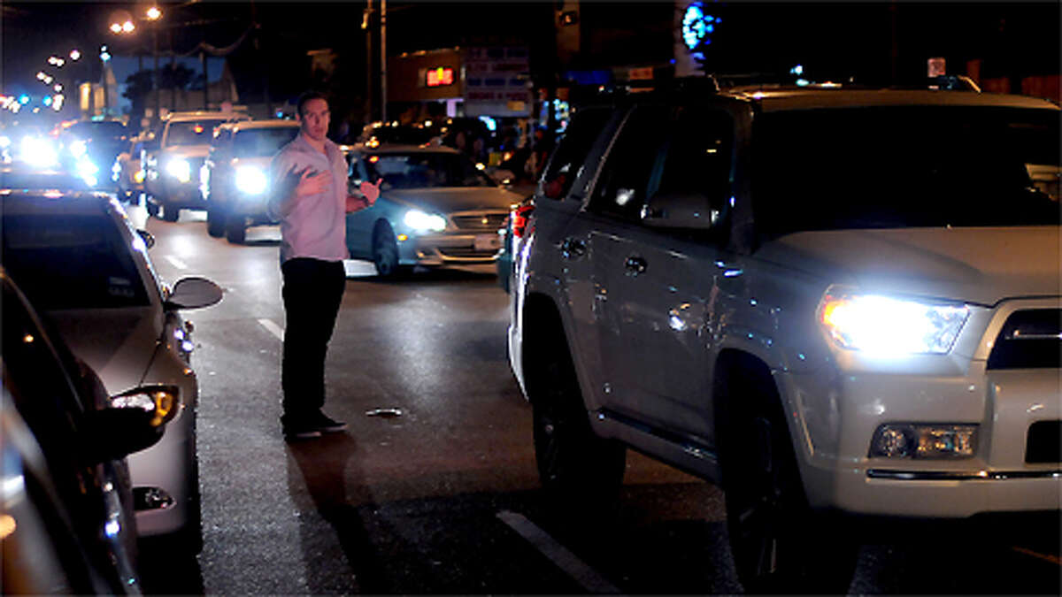 A man helps his friend squeeze into a legal parking space on Washington Avenue west of Shepherd Friday Nov. 09,2012.