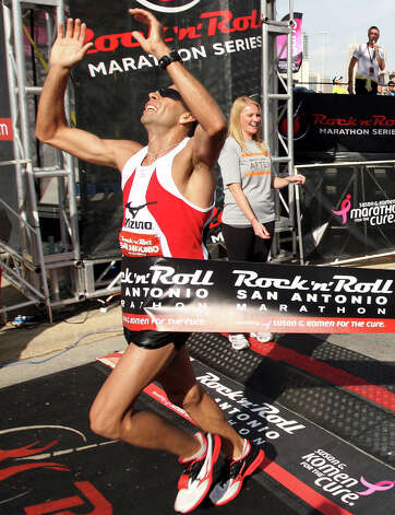 Jose Munoz, of San Antonio, crosses the finish line at the Rock 'n' Roll San Antonio Marathon and 1/2 Marathon, Sunday, Nov. 11, 2012. Munoz came in first place in the men's marathon division with a time of 2:27:51. Photo: Jerry Lara, San Antonio Express-News / © 2012 San Antonio Express-News