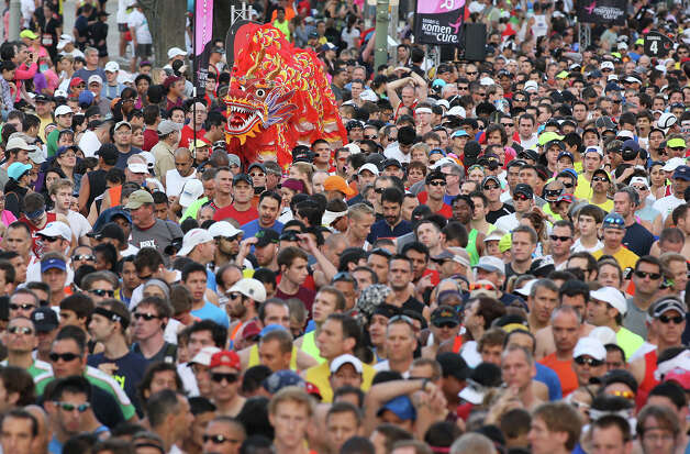 A group of runners carry a Chinese dragon costume as 25,000 runners line up to participate in the Rock 'n' Roll San Antonio Marathon and 1/2 Marathon, Sunday, Nov. 11, 2012. Photo: Jerry Lara, San Antonio Express-News / © 2012 San Antonio Express-News