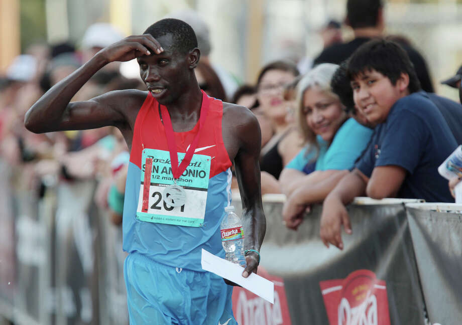 Holding a first place check, Stanley Biwott wipes sweat off his face, after finishing the half marathon with a time of 1:01:09 in the Rock 'n' Roll San Antonio Marathon and 1/2 Marathon, Sunday, Nov. 11, 2012. Photo: Jerry Lara, San Antonio Express-News / © 2012 San Antonio Express-News