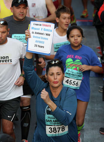 Rosabel Gabriel holds up a tribute while runing in the half marathon of the Rock 'n' Roll San Antonio Marathon and 1/2 Marathon, Sunday, Nov. 11, 2012. Photo: Jerry Lara, San Antonio Express-News / © 2012 San Antonio Express-News