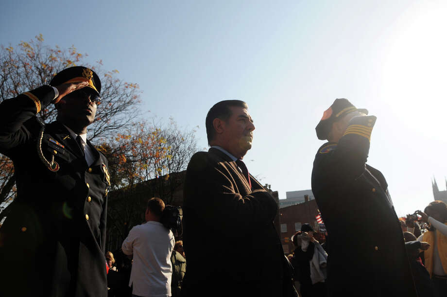 Archie Elam, Mayor Michael Pavia and Stamford Police Chief Jon Fontneau salute as the flag is raised during Stamford's Annual Veterans Day Parade from Hoyt Street to Veterans Park in Stamford, Conn., Nov. 11, 2012. Photo: Keelin Daly / Stamford Advocate Freelance