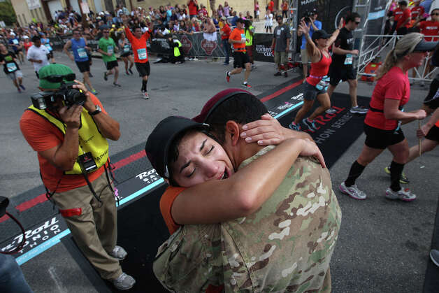 At the finish line, Sgt. Jonathan Gillis hugs his wife, Giselle, after she finished the half marathon in the Rock 'n' Roll San Antonio Marathon and 1/2 Marathon, Sunday, Nov. 11, 2012. Gilles, who was deployed to Afghanistan with the Texas Army National Guard, surprised his wife at the event. He arrived with his company to Camp Atterbury, Indiana last week but told his wife that his arrival would be delayed due to dental surgery. Photo: Jerry Lara, San Antonio Express-News / © 2012 San Antonio Express-News