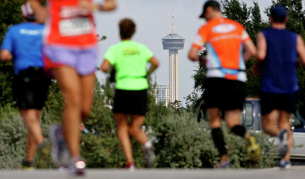 A view of the Tower of the Americas as runners make their way on Mission Road during the Rock 'n' Roll San Antonio Marathon and 1/2 Marathon Sunday Nov. 11, 2012. Photo: Edward A. Ornelas, San Antonio Express-News / © 2012 San Antonio Express-News