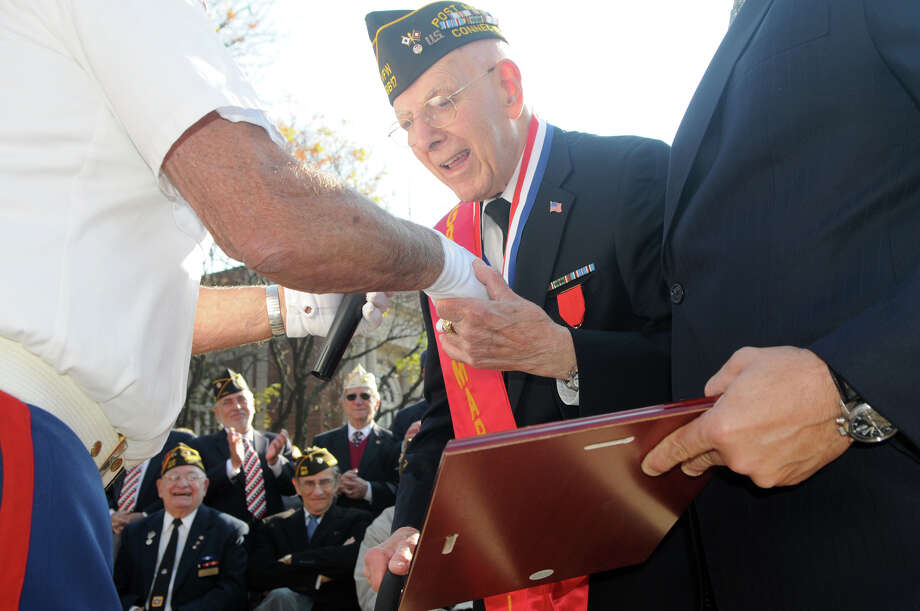 Grand Marshal Robert Castrignano, assisted by his son also Robert Castrignano, receives a plaque and recognition from Pasquale Battinelli, left, after Stamford's Annual Veterans Day Parade from Hoyt Street to Veterans Park in Stamford, Conn., Nov. 11, 2012. Photo: Keelin Daly / Stamford Advocate Freelance