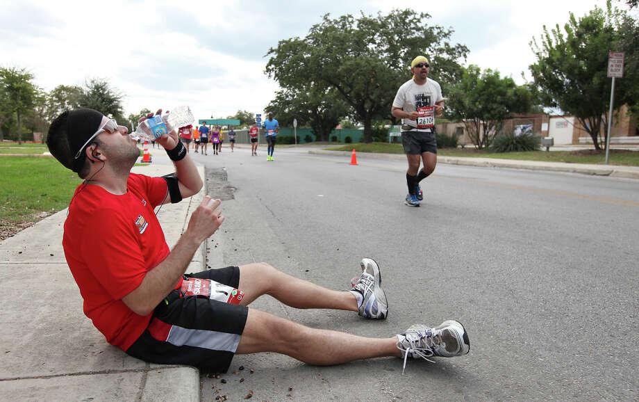 A runner takes a break on Mission Road during the Rock 'n' Roll San Antonio Marathon and 1/2 Marathon Sunday Nov. 11, 2012. Photo: Edward A. Ornelas, San Antonio Express-News / © 2012 San Antonio Express-News
