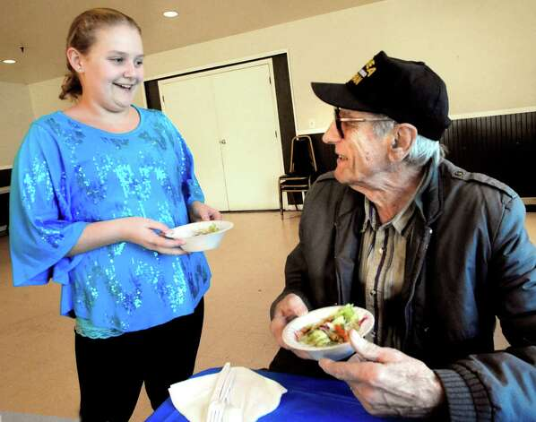 Elissa Jasmin, 9, serves David Demilio, a veteran of the Korean War, at the American Letgion Post No. 60 dinner in Danbury Sunday, Nov. 11, 2012. Photo: Michael Duffy / The News-Times