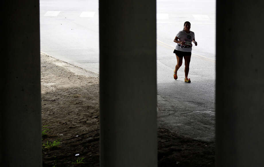 A runner passes under Interstate 10 during the Rock 'n' Roll San Antonio Marathon and 1/2 Marathon Sunday Nov. 11, 2012. Photo: Edward A. Ornelas, San Antonio Express-News / © 2012 San Antonio Express-News