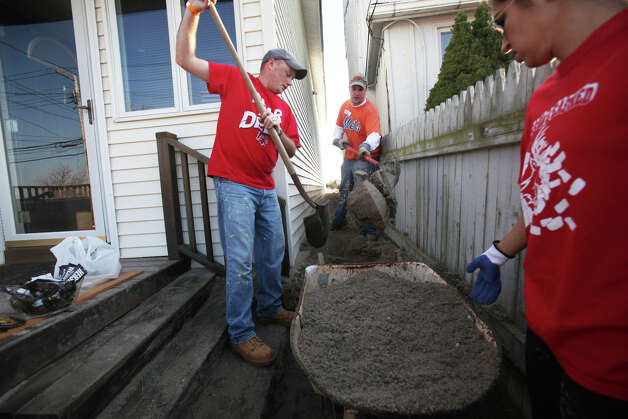 Volunteers, from left,  Justin Carroll, of Stratford, Mike Rupp, of Fairfield,  and Sarah Stempien, of Greenwich,  remove sand from a home on Fairfield Beach Road in Fairfield, Conn. on Sunday, November 11, 2012. Photo: BK Angeletti, B.K. Angeletti / Connecticut Post freelance B.K. Angeletti