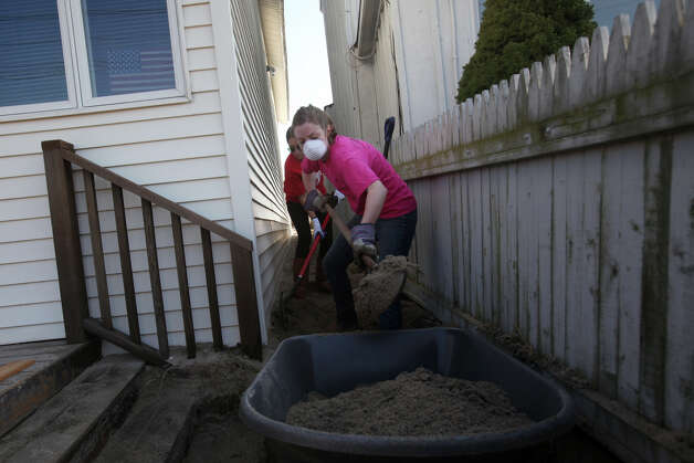 Volunteers and Fairfield Alumni, Mary McGrath, of Boston, in front, and Sarah Stempien, of Greenwich, remove sand from a home on Fairfield Beach Road in Fairfield, Conn. on Sunday, November 11, 2012. Photo: BK Angeletti, B.K. Angeletti / Connecticut Post freelance B.K. Angeletti