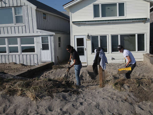 Volunteers and Fairfield Alumni, Ruby Mateo, of Middlebury, left, and Patrick Hendrickson, of Southport, remove sand from a home on Fairfield Beach Road in Fairfield, Conn. on Sunday, November 11, 2012. Photo: BK Angeletti, B.K. Angeletti / Connecticut Post freelance B.K. Angeletti