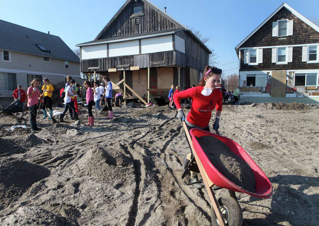 Volunteer Amanda Sullivan, of Stamford, right, removes sand from a home on Fairfield Beach Road in Fairfield, Conn. on Sunday, November 11, 2012. Photo: BK Angeletti, B.K. Angeletti / Connecticut Post freelance B.K. Angeletti