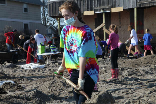 Volunteer Maddie O'Connell, 13, of Fairfield,  removes sand from a home on Fairfield Beach Road in Fairfield, Conn. on Sunday, November 11, 2012. Photo: BK Angeletti, B.K. Angeletti / Connecticut Post freelance B.K. Angeletti
