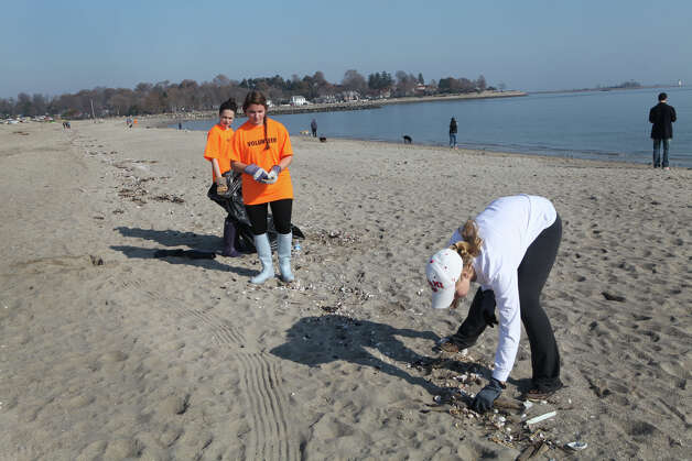 Volunteers, from left, Erin Valade, 15, Annie Silk, 15, and Timoney Campbell, 17, all of Fairfield, clean up Jennings Beach in Fairfield, Conn. on Sunday, November 11, 2012. The girls were part of a effort of 1000 volunteers to help residents after storm Sandy. Photo: BK Angeletti, B.K. Angeletti / Connecticut Post freelance B.K. Angeletti