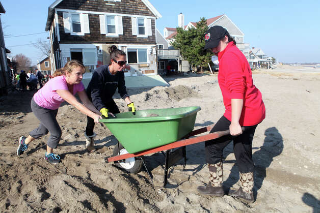 Volunteers remove sand from homes in Fairfield, Conn. on Sunday, November 11, 2012. The girls were part of a effort of 1000 volunteers to help residents after storm Sandy. Photo: BK Angeletti, B.K. Angeletti / Connecticut Post freelance B.K. Angeletti