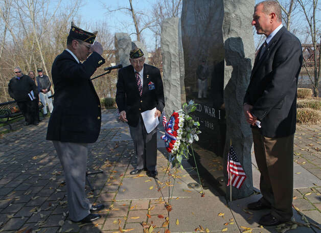 Veteran Dennis Salzar, left,  presents the Memorial Wreath during the annual American Legion Post 16's Veterans Day Ceremony at Veterans Memorial Park in Shelton, Conn. on November 11, 2012. Mayor Mark Lauretti stands right and Veteran Alphonse Sabetta , center, is the master of ceremonies. Photo: BK Angeletti, B.K. Angeletti / Connecticut Post freelance B.K. Angeletti