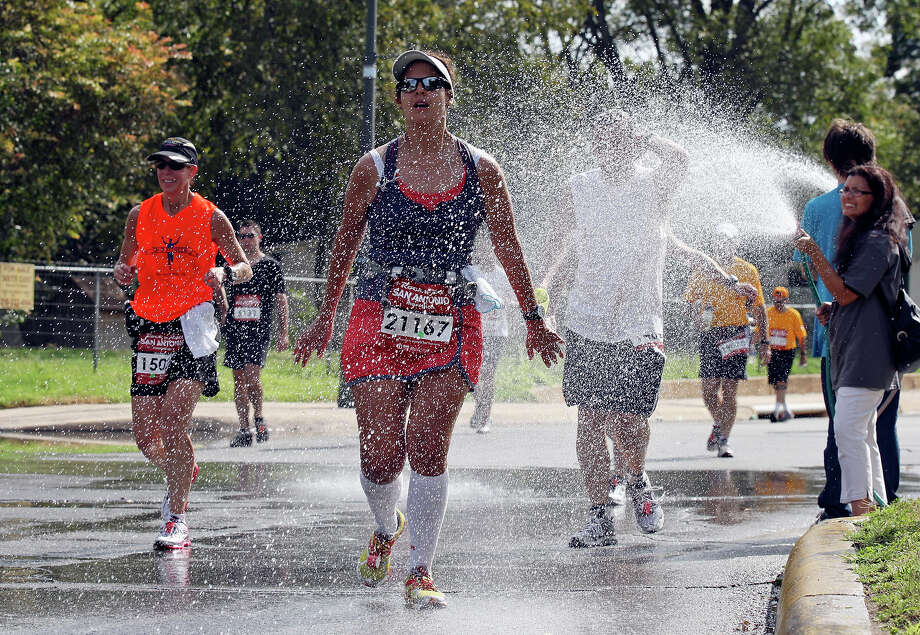 Celinda Guerra and other marathon runners are sprayed with water during the Rock 'n' Roll San Antonio Marathon and 1/2 Marathon Sunday Nov. 11, 2012. Guerra 's marathon time was 4:52:39. Photo: Edward A. Ornelas, San Antonio Express-News / © 2012 San Antonio Express-News
