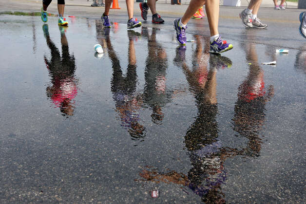 Marathon runners are reflected in water along Mission Road during the Rock 'n' Roll San Antonio Marathon and 1/2 Marathon Sunday Nov. 11, 2012. Photo: Edward A. Ornelas, San Antonio Express-News / © 2012 San Antonio Express-News
