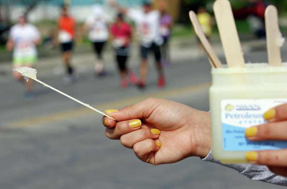 A volunteer hands out petroleum jelly to marathon runners during the Rock 'n' Roll San Antonio Marathon and 1/2 Marathon Sunday Nov. 11, 2012. Photo: Edward A. Ornelas, San Antonio Express-News / © 2012 San Antonio Express-News