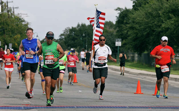 Marathon runner Joseph Lee Ortiz carries an American flag during the Rock 'n' Roll San Antonio Marathon and 1/2 Marathon Sunday Nov. 11, 2012.  Ortiz's marathon time was 5:17:20. Photo: Edward A. Ornelas, San Antonio Express-News / © 2012 San Antonio Express-News