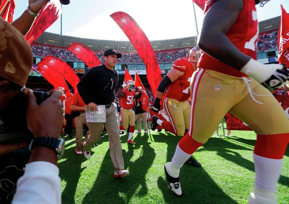 San Francisco 49ers head coach Jim Harbaugh and his team run onto the field during introductions before the start of an NFL football game against the St. Louis Rams in San Francisco, Sunday, Nov. 11, 2012. Photo: Marcio Jose Sanchez, Associated Press / AP