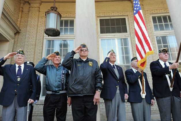 Veterans of the Greenwich American Legion Post 29 salute the flag for Veterans Day event in front of the War Memorial on Greenwich Avenue in Greenwich, Conn., Sunday, Nov. 11, 2012. Photo: Helen Neafsey / Greenwich Time