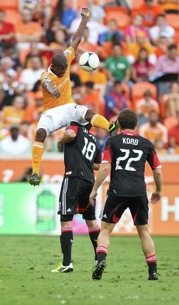 Houston Dynamo midfielder Boniek Garcia, top, jumps over D.C. United midfielder Nick DeLeon to contr