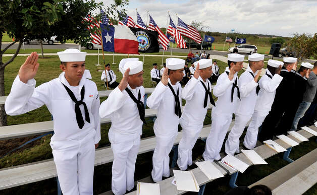 Sailors raise their hands to take the Immigration and Naturalization Oath to become United States citizens Sunday during the Veterans Day ceremony at Fort Sam Houston National Cemetery. Photo: Robin Jerstad/For The Express-Ne