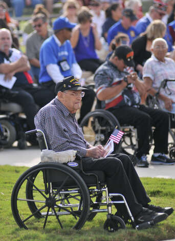 Navy and Korean War veteran Leon Clerico holds a small flag while attending the Veterans Day ceremony at Fort Sam Houston Sunday morning.. Photo: Robin Jerstad/For The Express-Ne