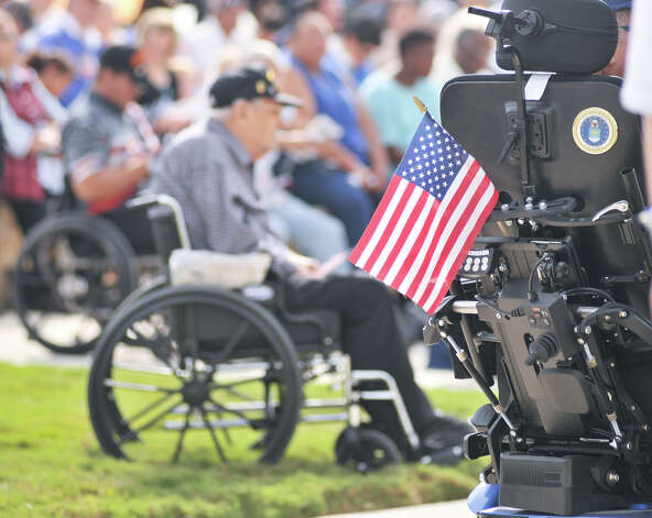 A small flag is attached to the back of a wheelchair during a Veterans Day ceremony at the Fort Sam Houston National Cemetery. Photo: Robin Jerstad/For The Express-Ne