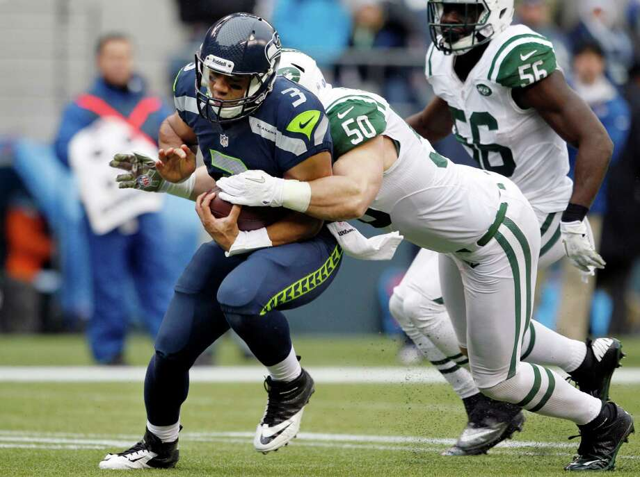 Seattle Seahawks quarterback Russell Wilson (3) is pulled down by New York Jets' Garrett McIntyre on a run for a first down late in the first half of an NFL football game, Sunday, Nov. 11, 2012, in Seattle. Photo: AP