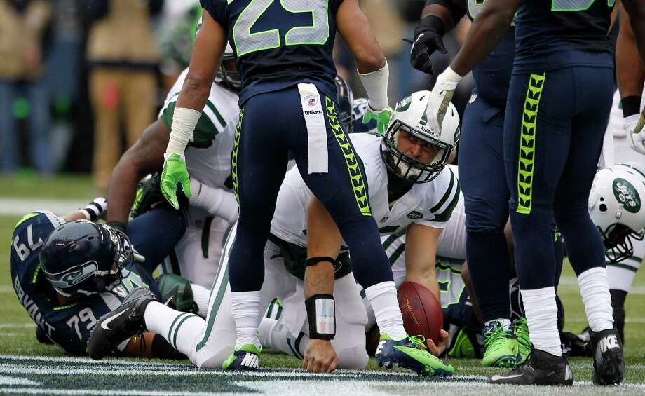 New York Jets quarterback Tim Tebow, center, gets up from a tackle after rushing against the Seattle Seahawks and being tackled by Seahawks' Red Bryant, left, during the first half of an NFL football game, Sunday, Nov. 11, 2012, in Seattle. Photo: AP