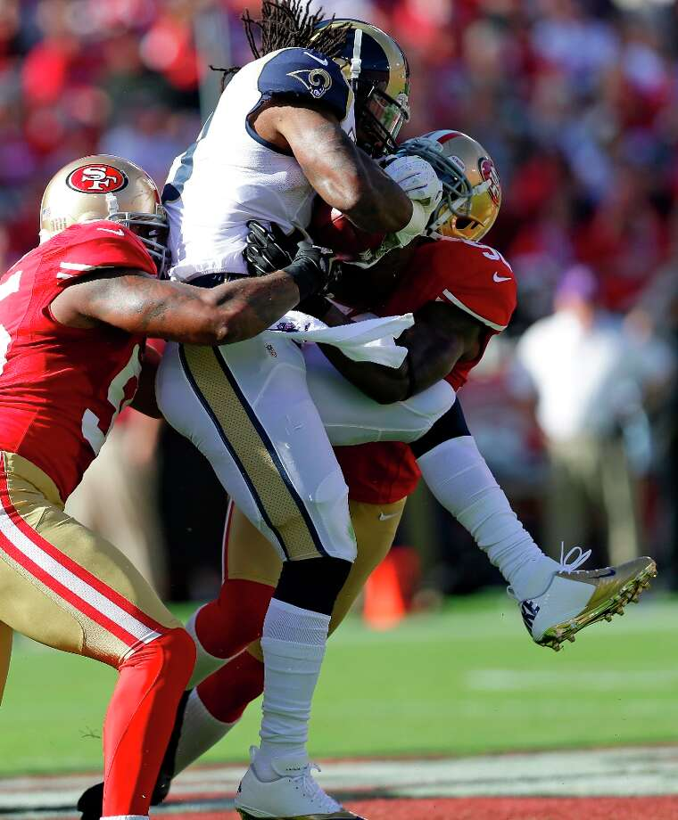 St. Louis Rams running back Steven Jackson, center, is brought down by San Francisco 49ers nose tackle Ricky Jean Francois, left, and linebacker Patrick Willis, right, during the first quarter of an NFL football game in San Francisco, Sunday, Nov. 11, 2012. Photo: Marcio Jose Sanchez, Associated Press / AP