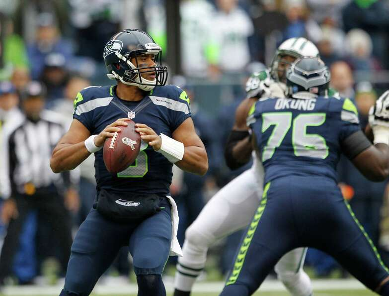 Seattle Seahawks quarterback Russell Wilson, left, looks to throw as Seahawks' Russell Okung (76) bl